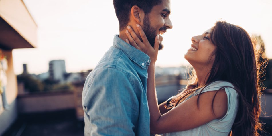 Beautiful young couple in love dating outdoors and smiling