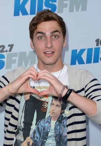 Big Time Rush-Darsteller Kendall Schmidt formt ein Herz mit seinen Händen.