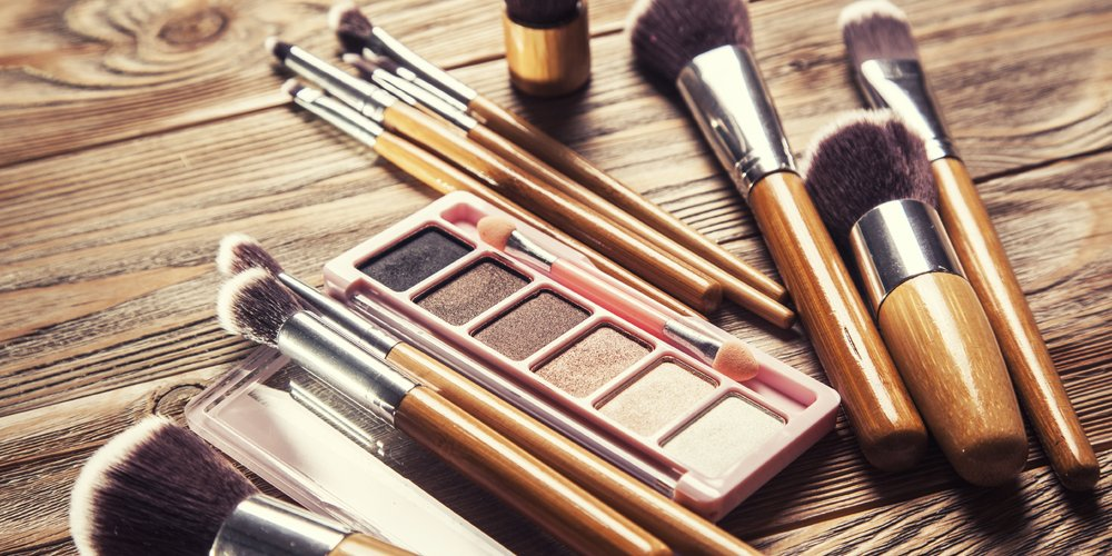 Brushes with cosmetics scattered chaotically on wooden background