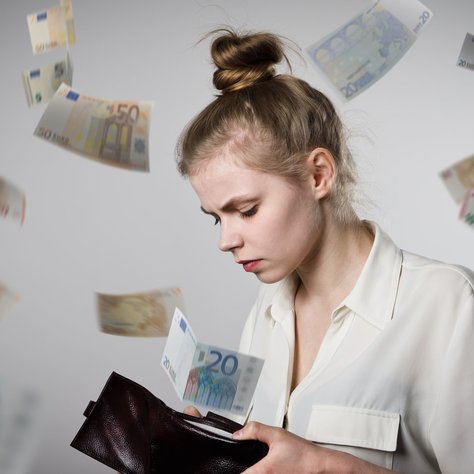 Worried slim woman is looking in a wallet. Euro are falling.