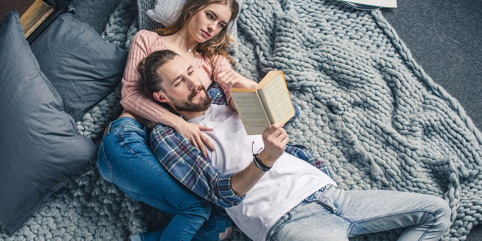 Beautiful young couple lying on knitted blanket and reading book