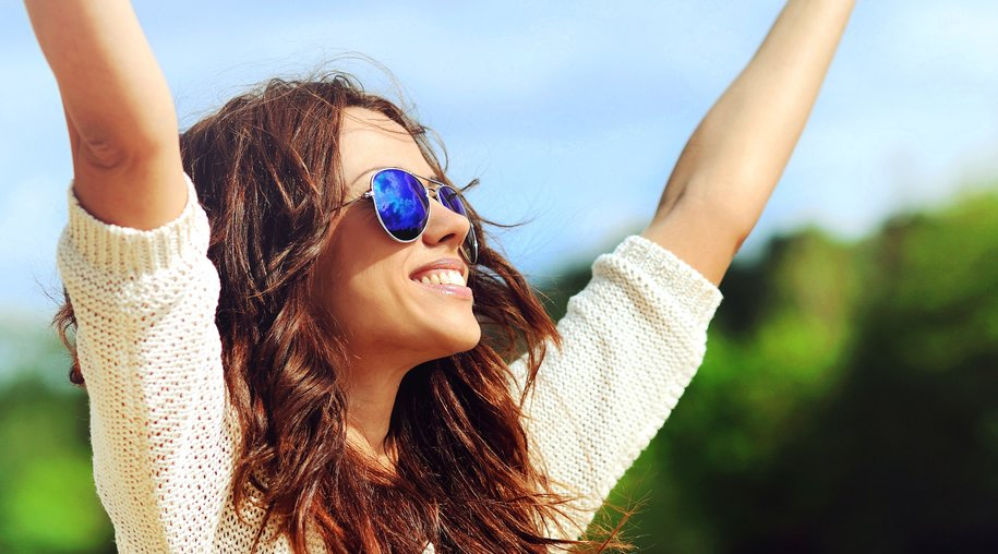 Attractive happy woman in sunglasses enjoying freedom outdoors with hand raised