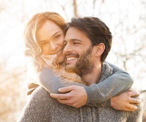 Closeup of smiling man carrying woman piggyback outdoor