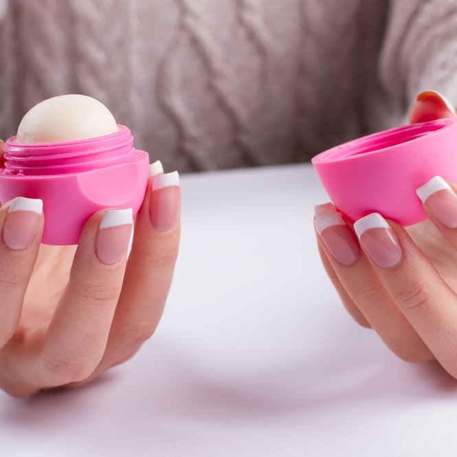 Pink lip balm in a beautiful female fingers. French manicure with lip gloss on the background of a knitted sweater. Winter care.