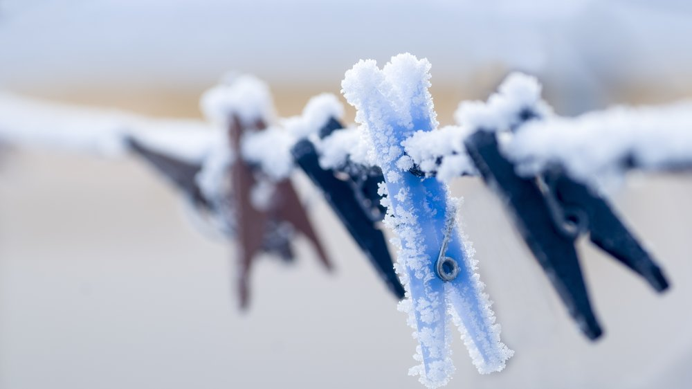 Frozen colorful clothes-pins on a rope at winter morning