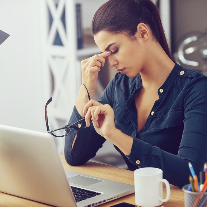 Frustrated young woman keeping eyes closed and massaging nose while sitting at her working place in office