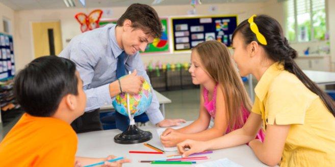 Montessori Schule: Lehrer erklärt Schülern etwas.