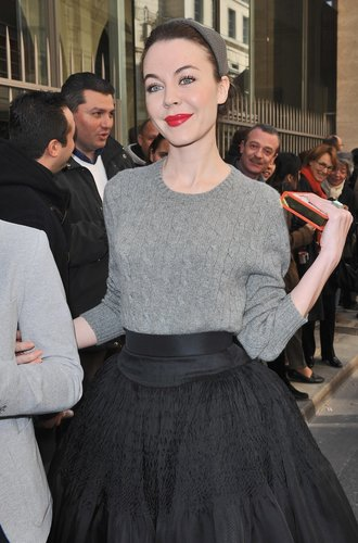 Der graue Pullover harmoniert mit dem schwarzen Rock und dem eleganten Hut.