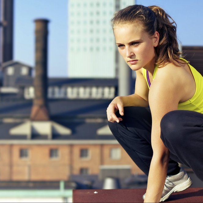 Young woman traceur balances on the edge of the roof of an industrial building while assessing the challenges of her immediate environment for parkour.