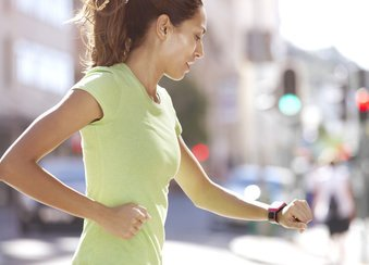 Läuferin schaut auf die Uhr