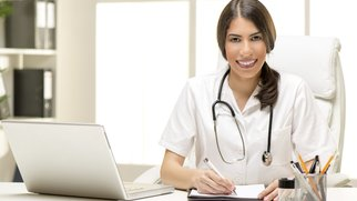 Beautiful young female doctor in her consulting room, sitting at the table in front of laptop and looking at the camera.