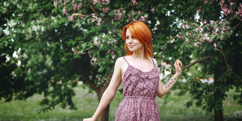 Young redhead woman near blossoming spring tree, natural beauty