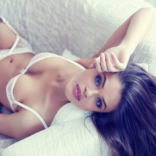close up portrait of beautiful alluring young woman in white sexy lingerie lying in sofa