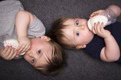 Zwillinge stillen oder Fläschchen geben