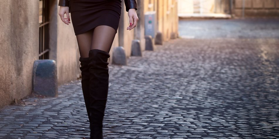 A gorgeous Russian girl, tall, with long brown hair and gray eyes, walks through the streets of the historic city of Rome, Italy. In the background behind it, the enormous columns of the Imperial Forums show themselves in all their grandeur and beauty. A tourist exploring the territory, happy.