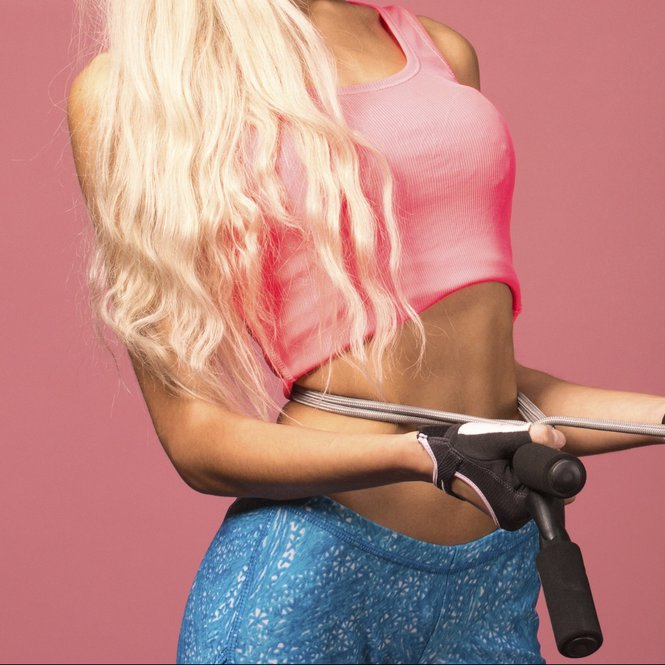 Portrait of young and healthy blonde with skipping rope on the pink background