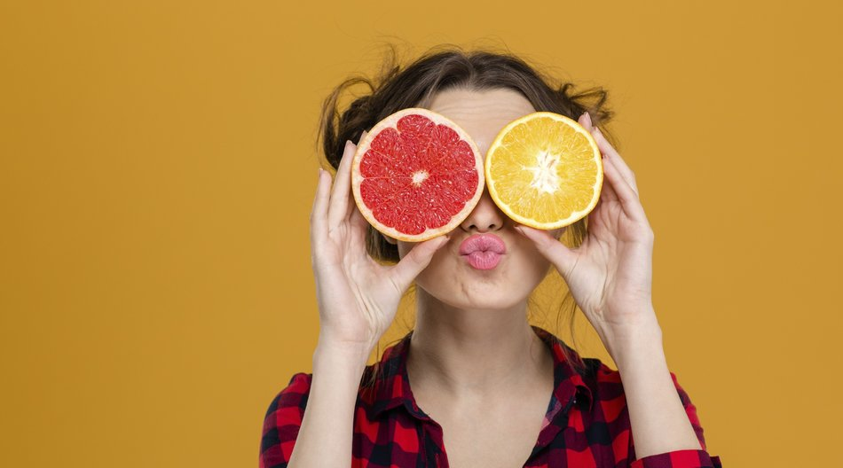 Funny playful young woman in checkered shirt holding halves of citrus fruits against her eyes and making duck face over yellow background