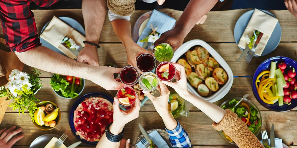 Friends toasting with fresh juice at dinner table
