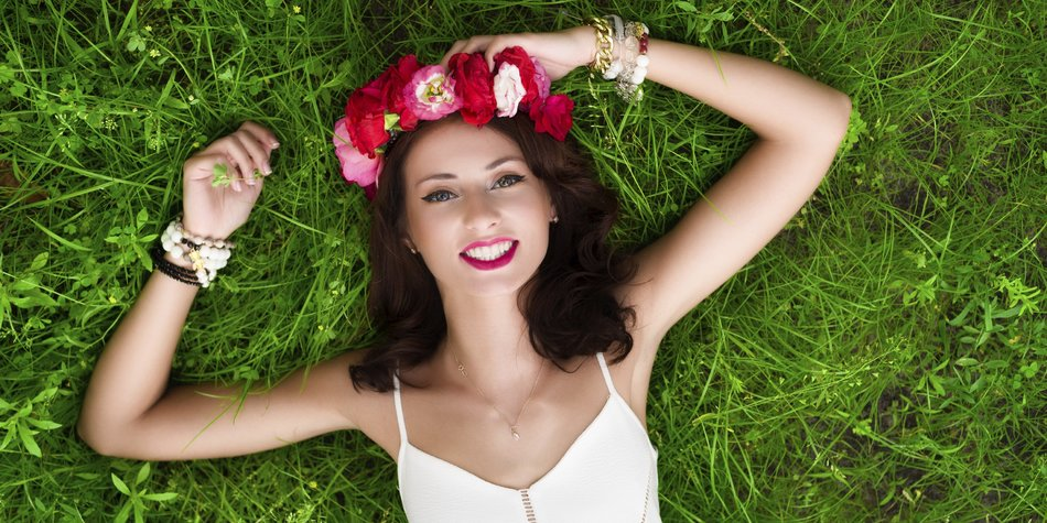 Gorgeous young woman in white dress with a flower wreath lying down on the grass.