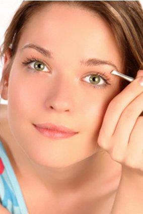 Frau zupft sich die Augenbraue