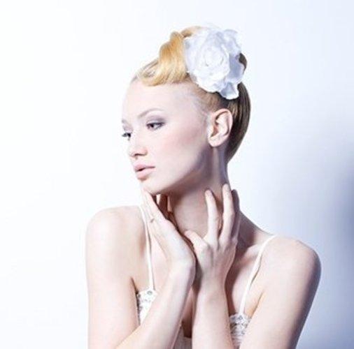 Edle Hochzeitfrisur: Dutt mit weißer Blume