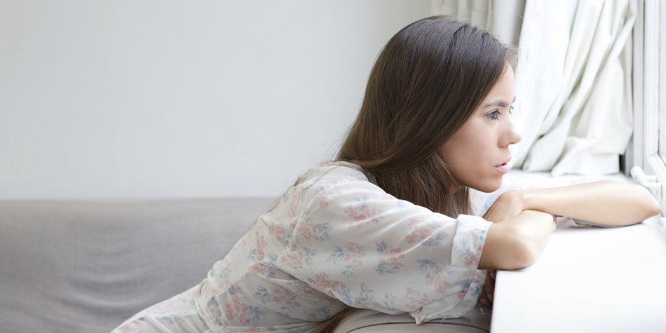 Profile portrait of a young woman sitting alone looking out window