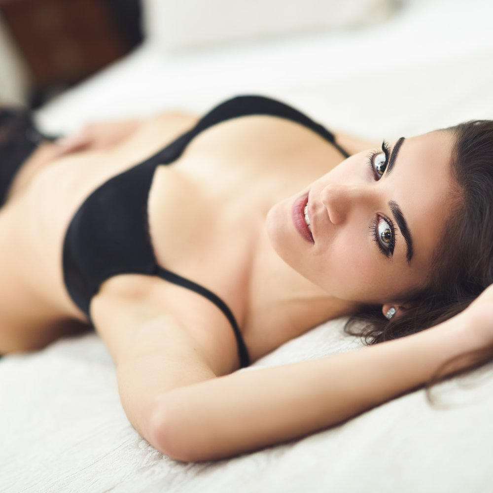 Close-up of sexy young woman in lingerie posing on the bed with beautiful green eyes. Brunette girl with black underwear in her bedroom