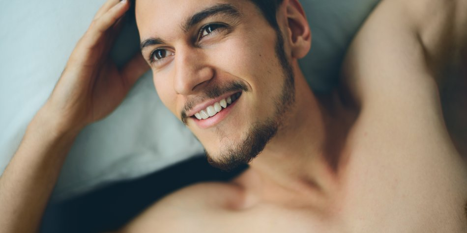 Handsome man lying on bed, happy smile waking up in the morning, attractive guy smiling in bedroom at home, sexy young male model