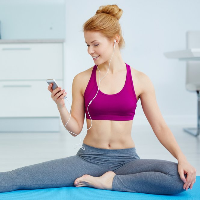Young woman with earphones listening to music while doing yoga exercise