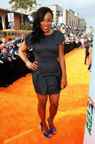Big Time Rush-Darstellerin Tanya Chisholm in einem schwarzen Kleid.
