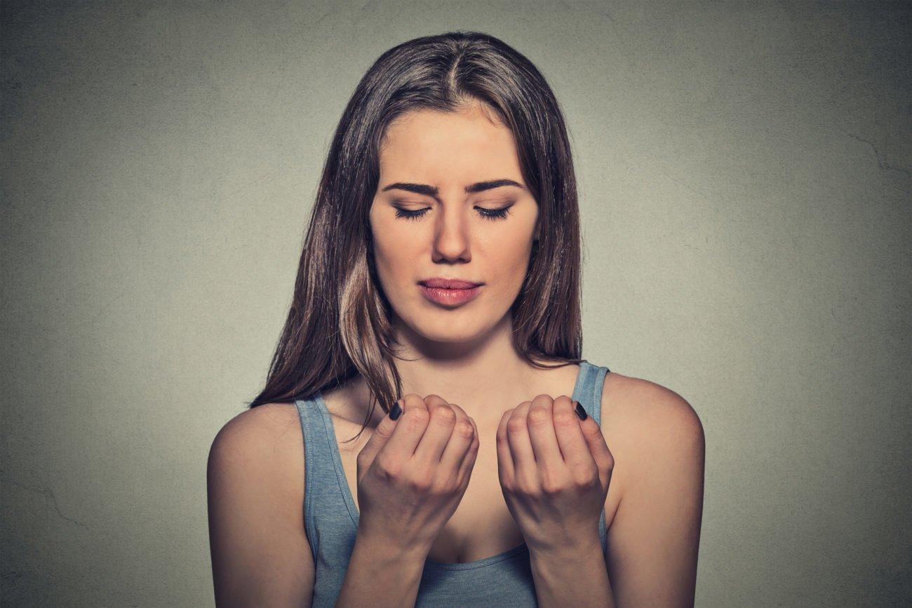 Frau schaut Fingernägel an