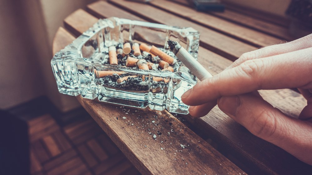 Man smoking a cigarette holding a burning filter tip in his hand alongside a glass ashtray full of ash and dead butts in a heavy smoker of addiction concept