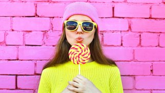 Fashion portrait pretty cool girl with lollipop over colorful pink background