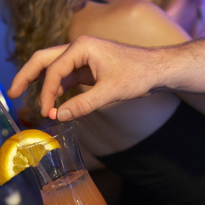 Close up Image Of Man Drugging Woman's Drink In Bar