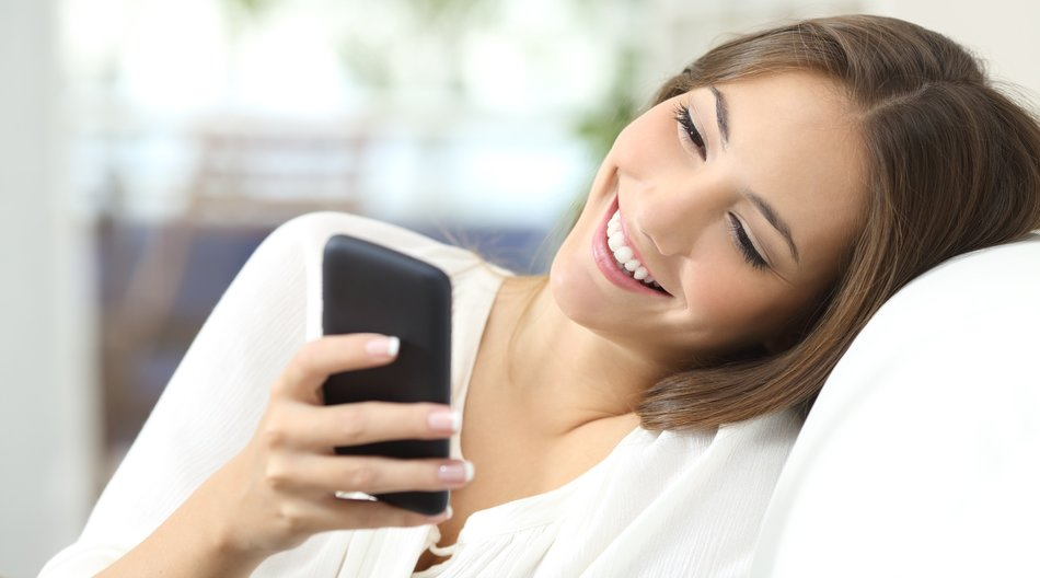 Happy girl texting on a mobile phone resting on a couch at home