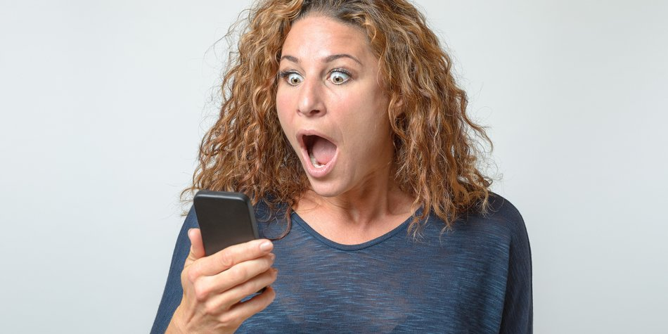 Shocked young woman staring at her mobile with her mouth wide open as she reads a text message on the screen