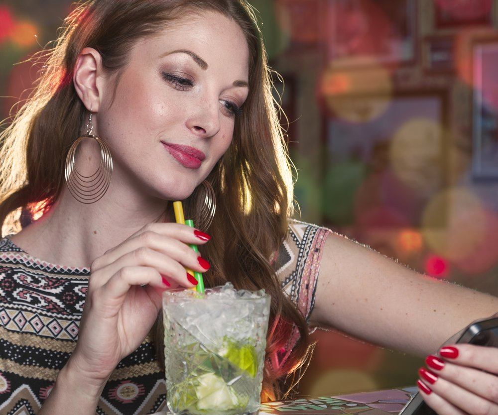 Woman reading a message on her mobile phone and drinking a mojito long drink while sitting at the counter of a club