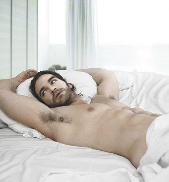 Muskulöser Mann im Bett