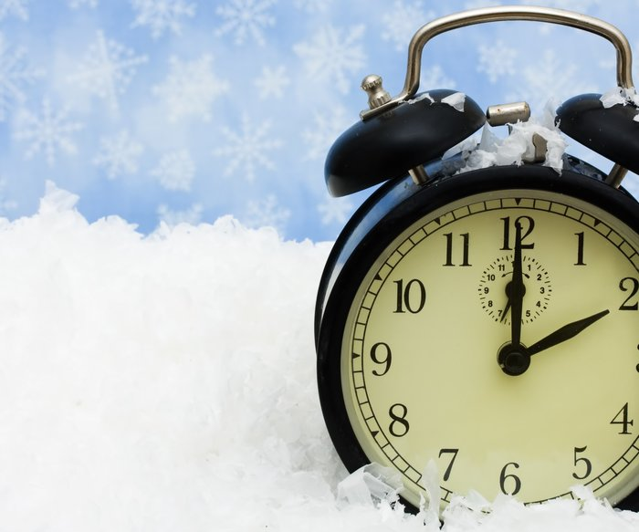 A black vintage face clock sitting on snow background, winter time