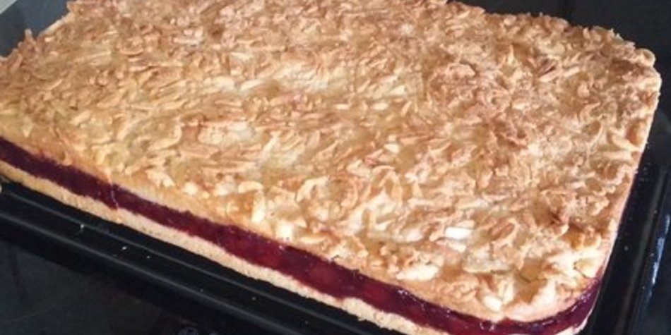 Gedeckter Frischkäse-Kirsch-Kuchen mit Mandeldecke