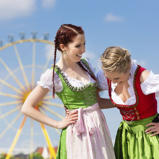 Young women in traditional Bavarian clothes - dirndl or tracht - on a festival or Oktoberfest
