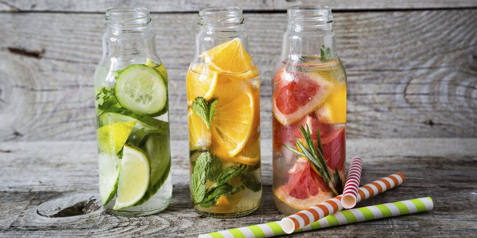 Selection of infused water in glass bottles, rustic wood background, copy space