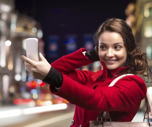 Beautiful young woman taking selfie in the city
