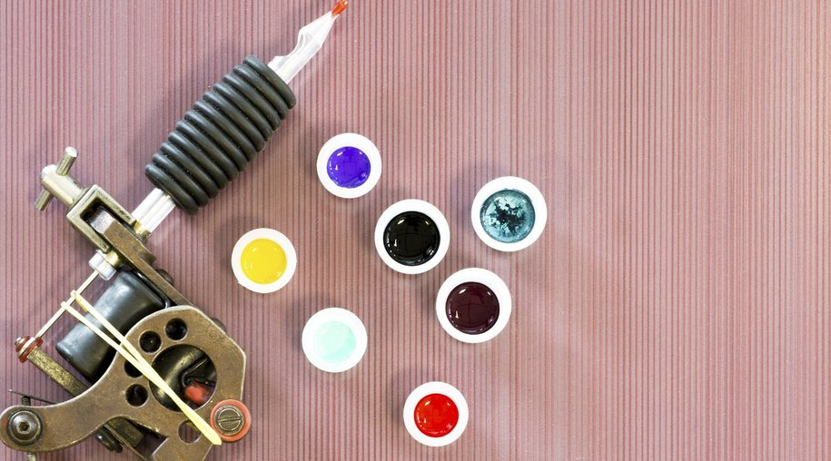 background of a tattoo session consists in a tattoo machine and ink cups colored