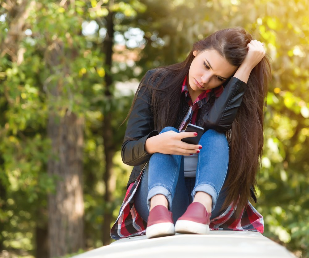 Girl sitting on stairs learns bad news by phone.