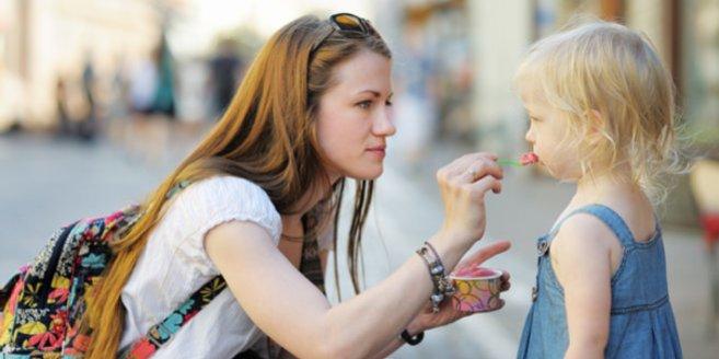 Babysitter füttert Kind mit Eis