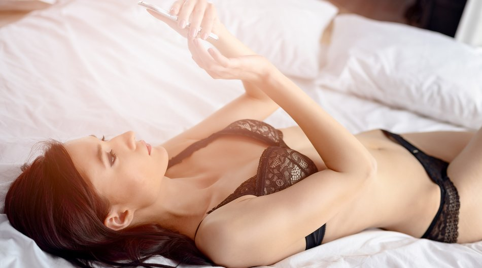 Woman reading a text message on her smartphone while relaxing on the bed in bedroom