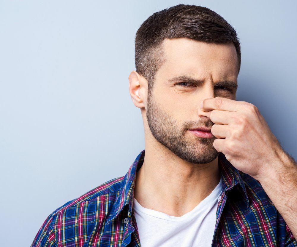 Portrait of frustrated young man in casual shirt holding nose and expressing negativity while standing against grey background