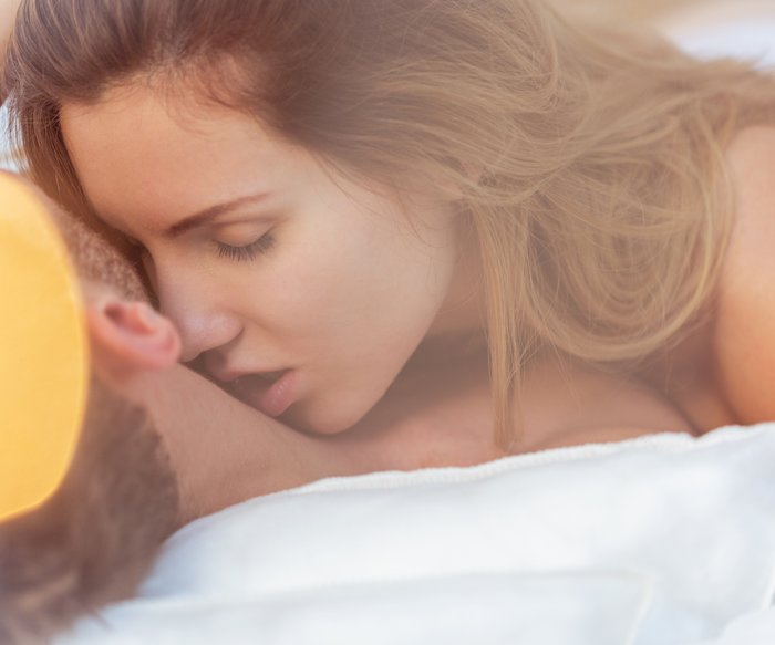 Close-up of alluring woman kissing male neck