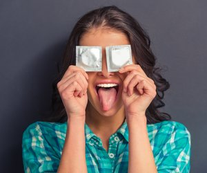 Portrait of attractive girl covering eyes with condoms and showing her tongue, against dark background